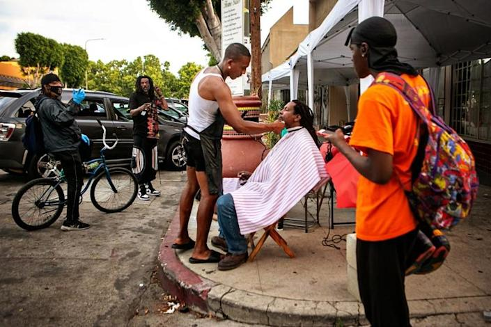 LEIMERT PARK, CA - JUNE 15: Jacket Rashad, a street barber, gives Karim Mejia Mawema, a food vendor, a haircut on Degnan Blvd. on Tuesday, June 15, 2021 in Leimert Park, CA. The Leimert Park community is excited for the reopening and is preparing for a huge Juneteenth block party. (Jason Armond / Los Angeles Times)