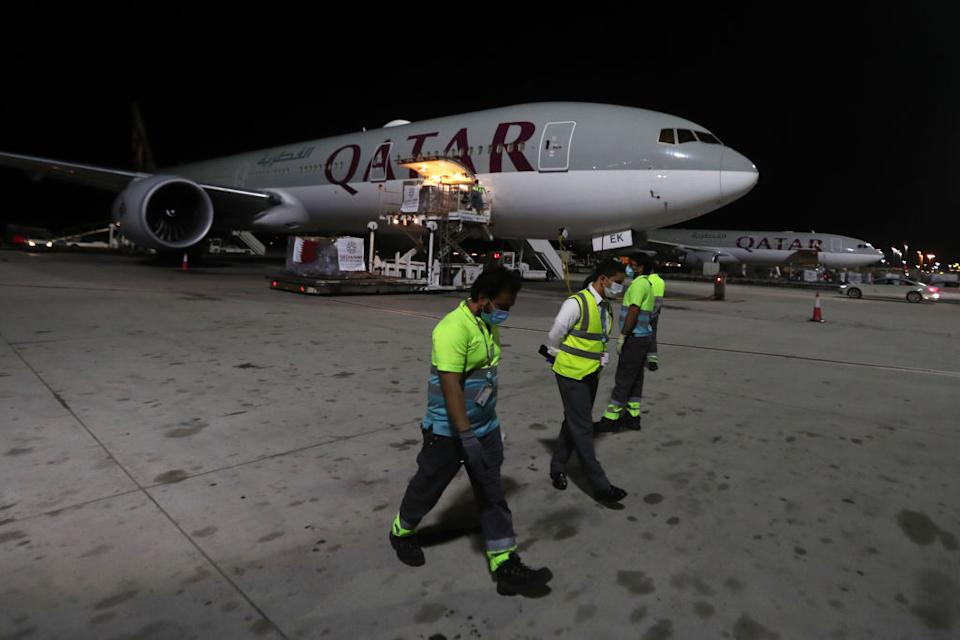 Airport workers wear masks as supplies to tackle coronavirus are loaded onto a Qatar Airways flight at Doha's Hamad International Airport. Source: Getty
