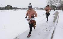 Same Reals, left, and Tyler Panko run shirtless through Wichita, Kan., Monday, Feb. 15, 2021. Reals said he tries to run a 5k on the coldest day of the year. The temperature during their run was -3, with a wind chill of -11. Frigid temperatures continue to grip with the middle of the continent. (Travis Heying/The Wichita Eagle via AP)