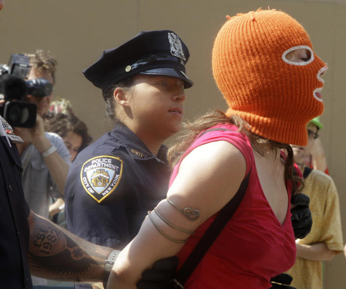 A protester is arrested during a demonstration in front of the Russian consulate in support of Russian punk band Pussy Riot, Friday, Aug. 17, 2012 in New York. A Russian judge found three members of the provocative punk band guilty of hooliganism on Friday, in one of the most closely watched cases in recent Russian history. The judge said the three band members committed hooliganism driven by religious hatred and offending religious believers. The three were arrested in March after a guerrilla performance in Moscow's main cathedral calling for the Virgin Mary to protect Russia against Vladimir Putin, who was elected to a new term as Russia's president a few days later.(AP Photo/Alex Katz)