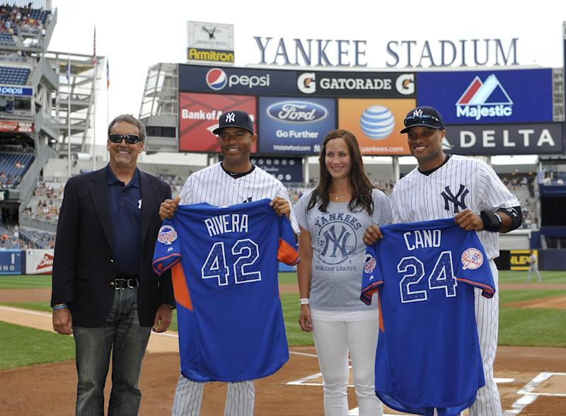 Representatives from Majestic give New York Yankees' Mariano Rivera (42) and Robinson Cano (24) their All-Star team shirts before a baseball game against the Minnesota Twins at Yankee Stadium, Sunday, July 14, 2013, in New York. (AP Photo/Kathy Kmonicek)