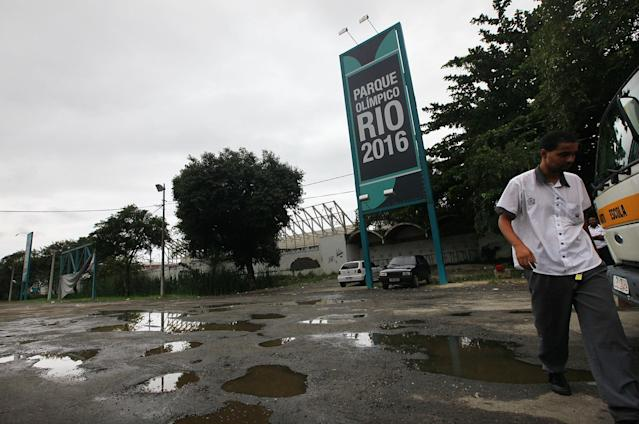 RIO DE JANEIRO, BRAZIL - APRIL 16: A man walks near the entrance to Olympic Park, the primary set of venues being built for the Rio 2016 Olympic Games, on April 16, 2014 in Rio de Janeiro, Brazil. More than 2,000 workers have been on strike at the site for the past two weeks in spite of an apparent new settlement. (Photo by Mario Tama/Getty Images)