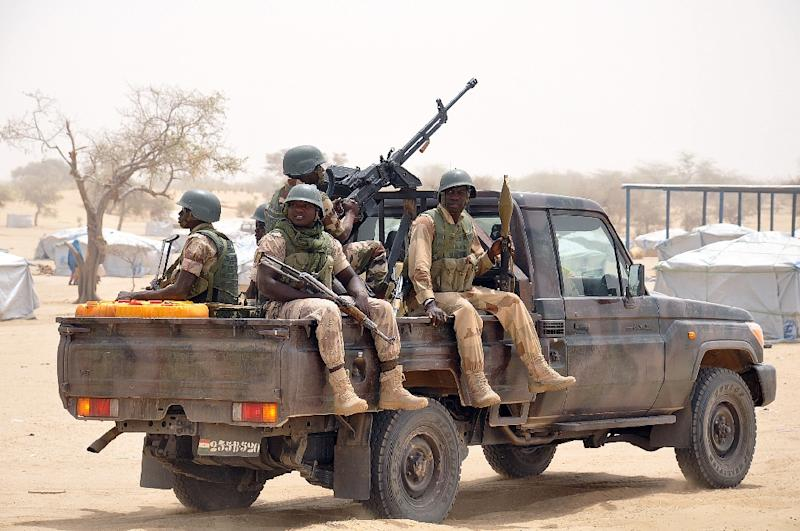 Nigerien soldiers patrol in a truck at Kabalewa Refugees Camp, where Nigerians fleeing from Boko Haram Islamists attacks are sheltered at Diffa in Niger Republic, on March 13, 2015
