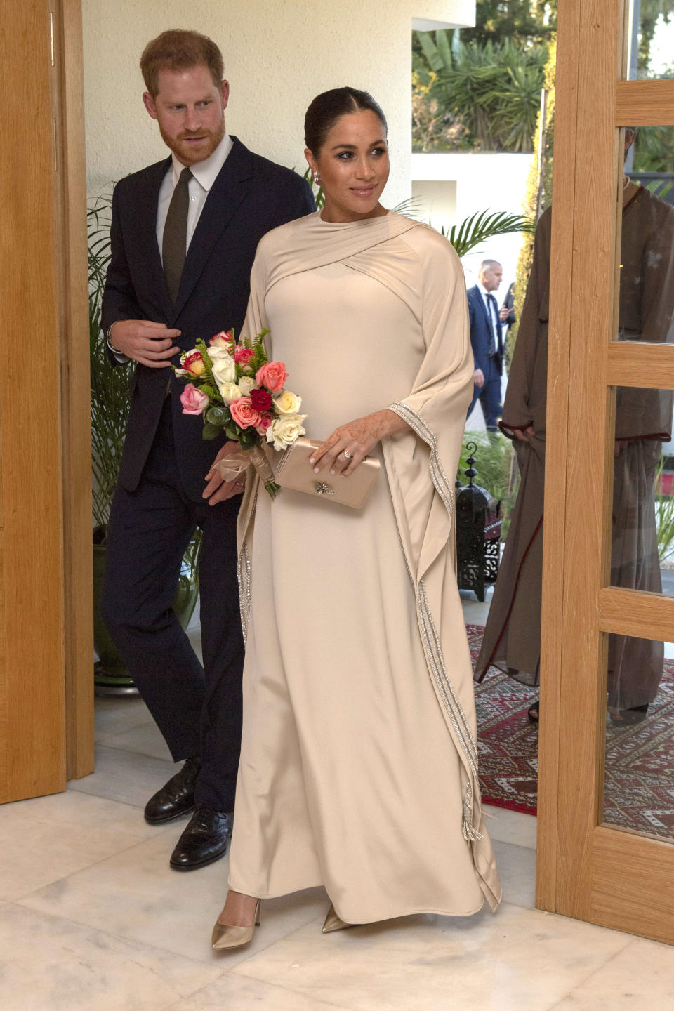 """<p>For the evening reception at the British residence in Rabat, Meghan wore a bespoke Dior gown with a draped neckline and beaded sleeves, with a gold clutch from the French fashion house and metallic court shoes. She wore her hair in a sleek bun and finished her look with her statement <a rel=""""nofollow noopener"""" href=""""https://www.maisonbirks.com/en/birks-snowflake-snowstorm-diamond-earrings-in-white-gold"""" target=""""_blank"""" data-ylk=""""slk:Birks Snowstorm earrings"""" class=""""link rapid-noclick-resp"""">Birks Snowstorm earrings</a>. [Photo: Getty] </p>"""