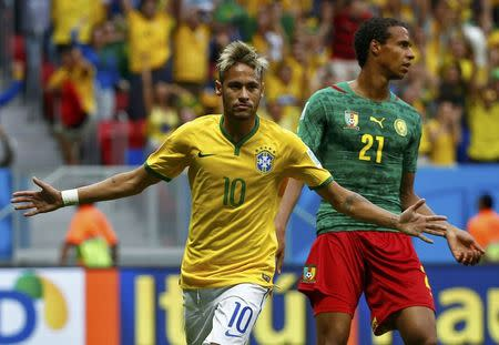 Brazil's Neymar celebrates past Cameroon's Joel Matip after scoring a goal during their 2014 World Cup Group A soccer match at the Brasilia national stadium in Brasilia June 23, 2014. REUTERS/Michael Dalder