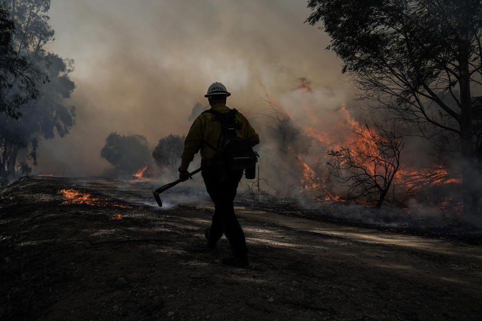 A firefighter prepares to put out hotspots while battling the Silverado Fire, Monday, Oct. 26, 2020, in Irvine, Calif. The fast-moving wildfire forced evacuation orders for 60,000 people in Southern California on Monday as powerful winds across the state prompted power to be cut to hundreds of thousands to prevent utility equipment from sparking new blazes. (AP Photo/Jae C. Hong)