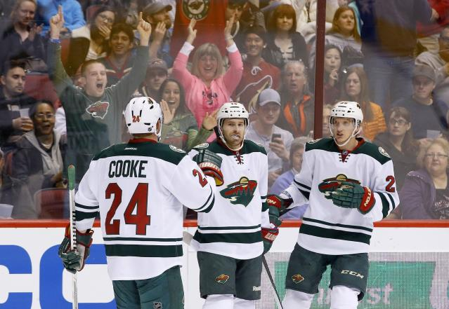 Minnesota Wild's Justin Fontaine, middle, celebrates his goal against the Phoenix Coyotes with teammates Matt Cooke (24) and Jonas Brodin, of Sweden, during the first period in an NHL hockey game Thursday, Jan. 9, 2014, in Glendale, Ariz. (AP Photo/Ross D. Franklin)