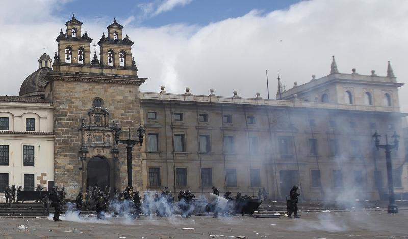 Riot police stand in the capital's main square during clashing with students in downtown Bogota, Colombia, Thursday, Aug. 29, 2013. Students are protesting in support of farmers who demand lower fertilizer prices, complain of being undercut by cheap imports from near and far of products including potatoes, onions and milk, and say their sector is being hurt by free trade and other agreements promoted by the government. (AP Photo/Fernando Vergara)