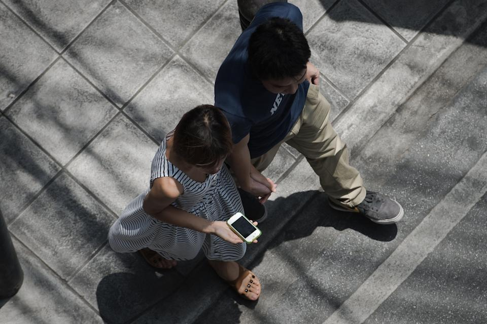 This picture taken on March 20, 2013 shows a woman holding her smartphone while walking with her partner in a street in Bangkok. A recent Facebook-sponsored study showed smartphone owners are often connected all day. People can be found glued to their smartphones at airports, on trains, in restaurants and even while walking on the street, creating a disconnection from their immediate surroundings. Smartphone sales are expected to continue to surge in 2013 with some 918 million units to be bought worldwide. AFP PHOTO / Nicolas ASFOURI (Photo by Nicolas ASFOURI / AFP) (Photo by NICOLAS ASFOURI/AFP via Getty Images)