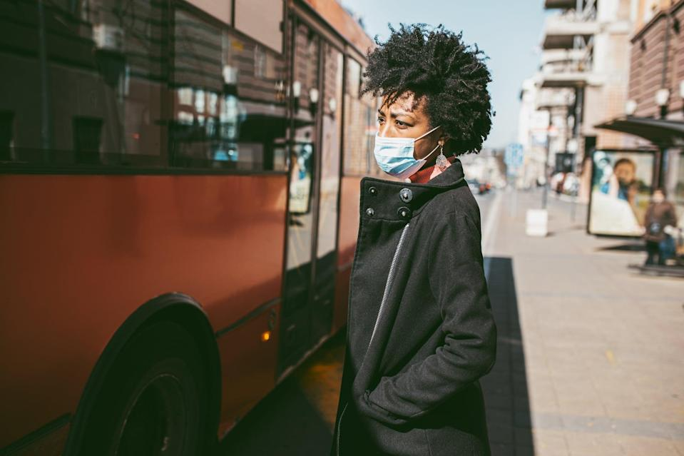 Young Afro American woman standing on city street with protective mask on her face and waiting for bus transportation. Virus pandemic and pollution concept.