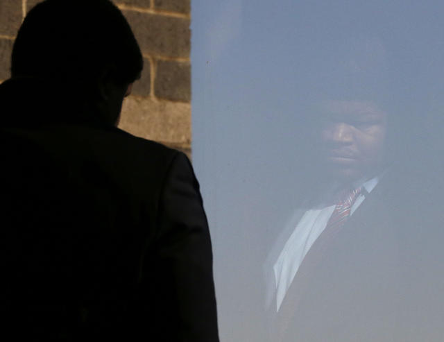 A faint reflection of former Dallas Cowboys Josh Brent is seen on glass as he looks out of a window in the hallway of the courthouse in Dallas, Tuesday, Jan. 21, 2014, as the jury is deliberates his intoxication manslaughter charge. Prosecutors accuse the former defensive tackle of drunkenly crashing his Mercedes near Dallas during a night out in December 2012, killing his good friend and teammate, Jerry Brown. (AP Photo/LM Otero)
