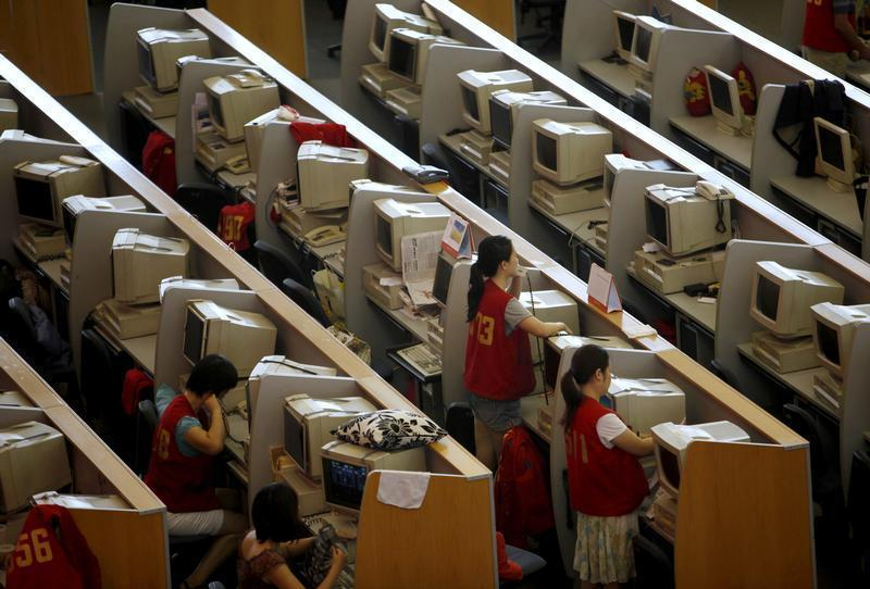 Brokers work next to their computers at the Shanghai Stock Exchange