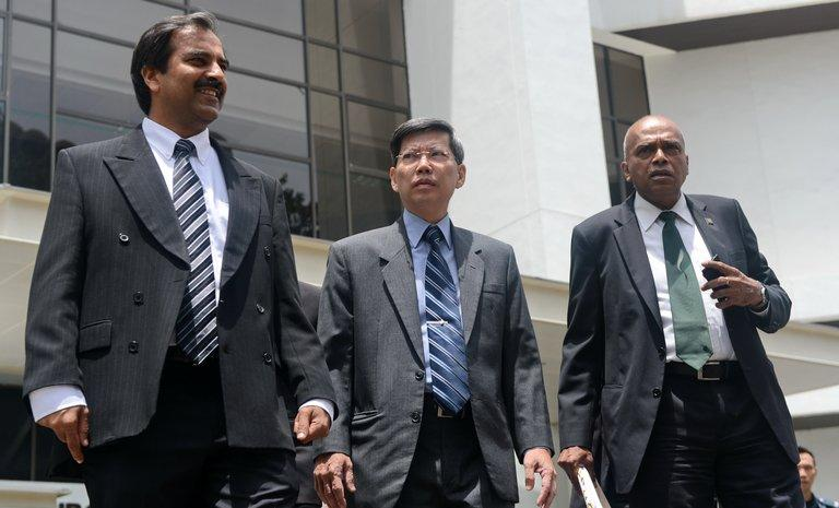 Peter Lim (C), Singapore's former civil defence chief,  leaves court with his two lawyers, on February 18, 2013
