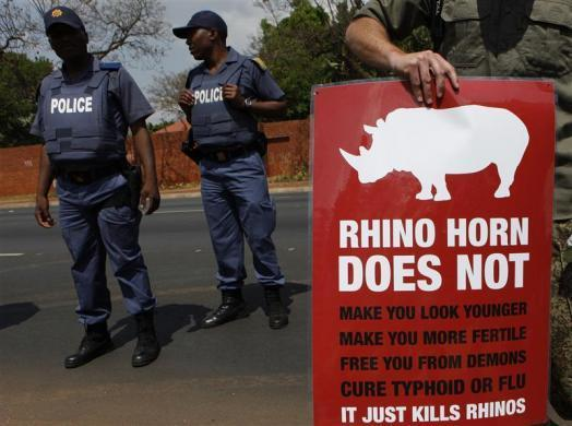 Policeman look on as a protester carries a placard calling for an end to rhino poaching, which threatens the survival of rhino species, outside the Chinese embassy in Pretoria September 22, 2011.