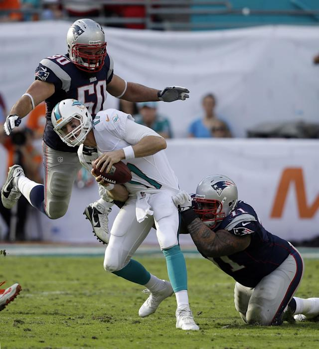 New England Patriots defensive tackle Sealver Siliga (71) and defensive end Rob Ninkovich (50) come down on Miami Dolphins quarterback Ryan Tannehill (17) for a sack during the second half of an NFL football game on Sunday, Dec. 15, 2013, in Miami Gardens, Fla. (AP Photo/Lynne Sladky)