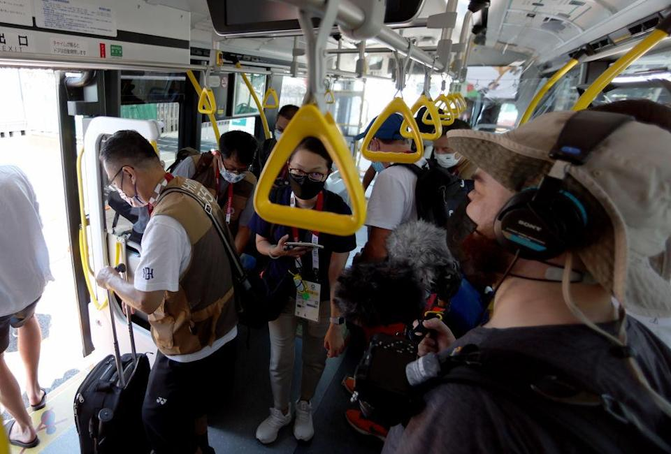 """Media members ride the bus from the Main Press Center at Tokyo Big Sight to the transport hub ahead of the Tokyo 2020 Olympic Games on July 22, 2021 in Tokyo, Japan.<span class=""""copyright"""">Elsa—Getty Images</span>"""