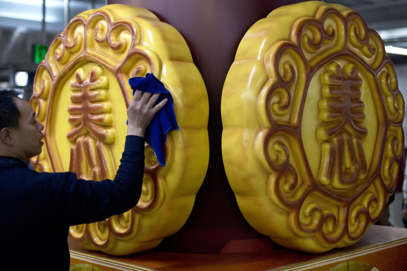 In this Wednesday, Sept. 11, 2013 photo, a cleaner wipes mooncake shaped advertisement decorations in a subway station in Beijing, China. The mooncake, a traditional Chinese pastry given as a gift during the Chinese mid-autumn festival, has become the unlikely latest casualty of Beijing's anti-corruption campaign. (AP Photo/Alexander F. Yuan)