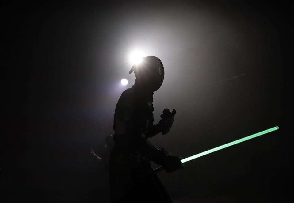 In this Sunday, Feb. 10, 2019, photo, a competitor battles during the national lightsabers tournament in Beaumont-sur-Oise, north of Paris. In France, lightsaber fighting is an official sport, recognized as such by the French Fencing Federation. The sport's practitioners, many but not all of the fans of 'Stars Wars,' have had to build the discipline's competition rules almost from scratch. (AP Photo/Christophe Ena)