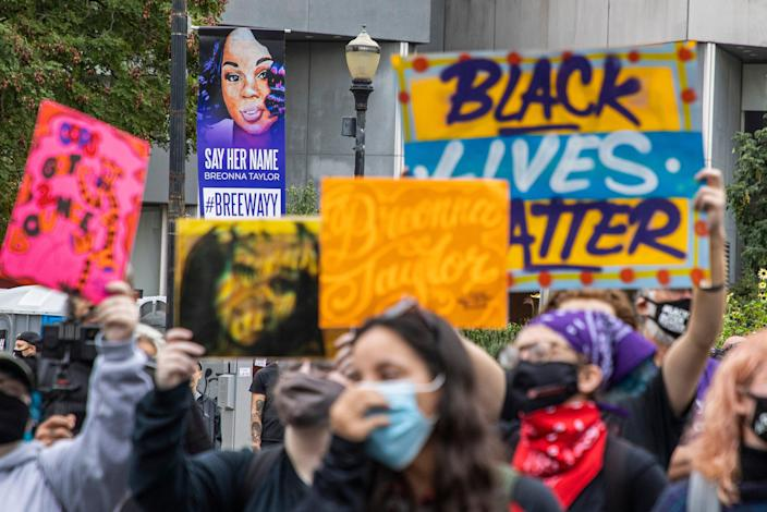 Protesters hold signs as they regroup at Jefferson Square Park following marches as a Breonna Taylor sign looks down upon them Wednesday. Sept. 23, 2020