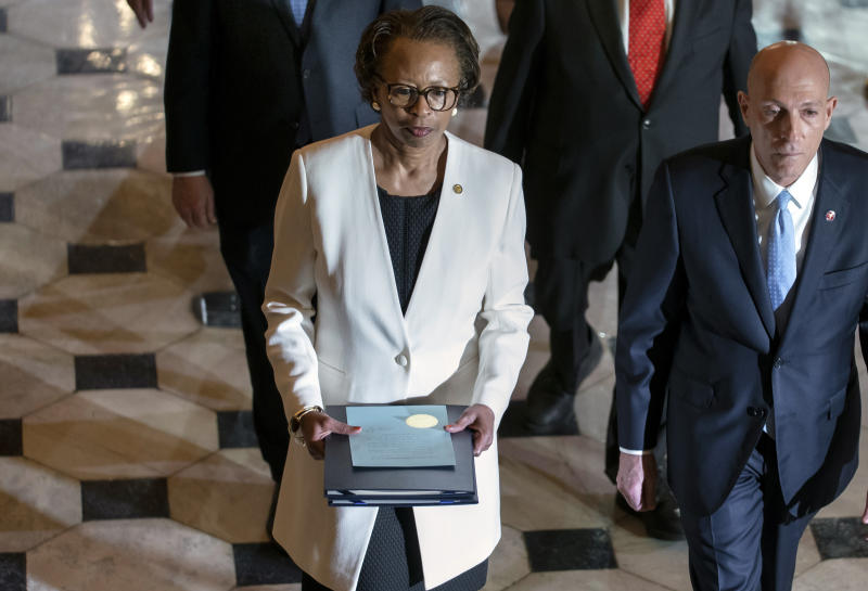 Clerk of the House Cheryl Johnson, center, with House Sergeant at Arms Paul Irving, right, pass through Statuary Hall at the Capitol to deliver the articles of impeachment against President Donald Trump to the Senate, on Capitol Hill in Washington, Wednesday, Jan. 15, 2020. (AP Photo/J. Scott Applewhite)