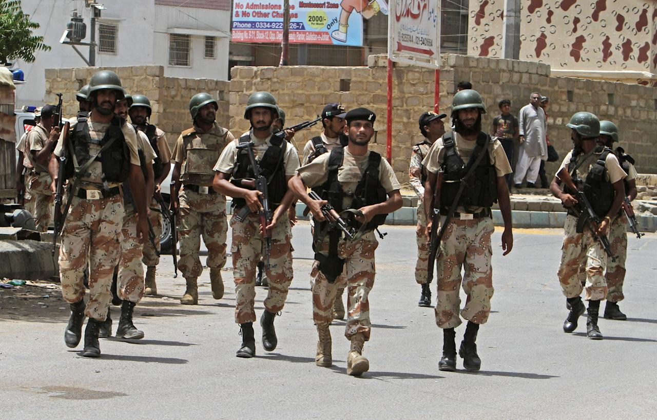 Pakistani security personnel inspect the site around a training center after gunmen attacked the facility in Karachi, Pakistan, Tuesday, June 10, 2014. Gunmen in Pakistan attacked a training facility near the Karachi airport on Tuesday, a spokesman said. The facility is roughly one kilometer (half mile) from the Karachi international airport. (AP Photo/Fareed Khan)