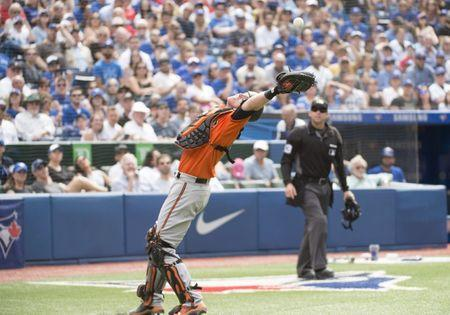 Jun 9, 2018; Toronto, Ontario, CAN; Baltimore Orioles catcher Chance Sisco (15) catches a foul ball for an out during the eighth inning against the Toronto Blue Jays at Rogers Centre. Mandatory Credit: Nick Turchiaro-USA TODAY Sports