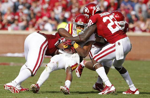 Iowa State's Aaron Wimberly, center, is tackled by Oklahoma defenders Chuka Ndulue, right, and Cortez Johnson, right, in the third quarter of an NCAA college football game in Norman, Okla. on Saturday, Nov. 16, 2013. Oklahoma won 48-10. (AP Photo/Alonzo Adams)