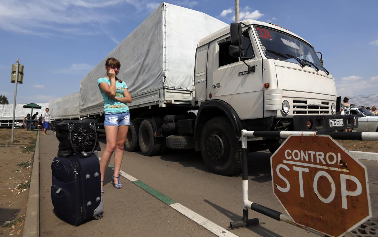 "Trucks of a Russian convoy carrying humanitarian aid for Ukraine drive onto the territory of a Russia-Ukraine border crossing point ""Donetsk"", as a woman waits for her son who has fled from fighting in eastern regions of Ukraine and is expected to cross the border, in Russia's Rostov Region, August 22, 2014. Ukraine declared on Friday that Russia had launched a ""direct invasion"" of its territory after Moscow sent a convoy of aid trucks across the border into eastern Ukraine where pro-Russian rebels are fighting government forces. REUTERS/Alexander Demianchuk (RUSSIA - Tags: TRANSPORT POLITICS CONFLICT SOCIETY CIVIL UNREST)"