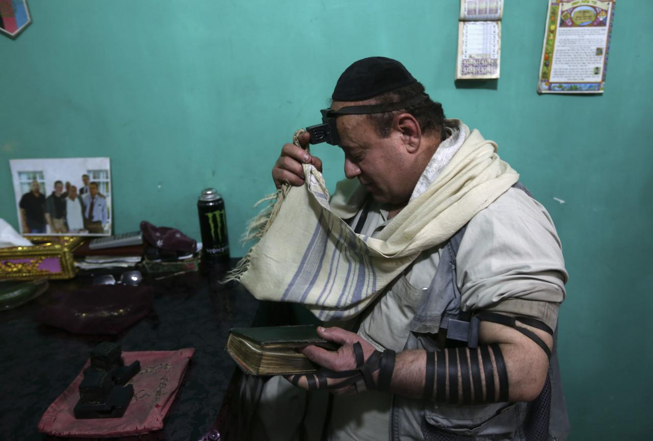Zabulon Simintov, an Afghan Jew, prays at his residence in Kabul November 5, 2013. In his 50s, Simintov is the last known Afghan Jew to remain in the country. He has become something of a celebrity over the years and his rivalry with the next-to-last Jew, who died in 2005, inspired a play. Picture taken November 5, 2013. REUTERS/Omar Sobhani (AFGHANISTAN - Tags: SOCIETY RELIGION)