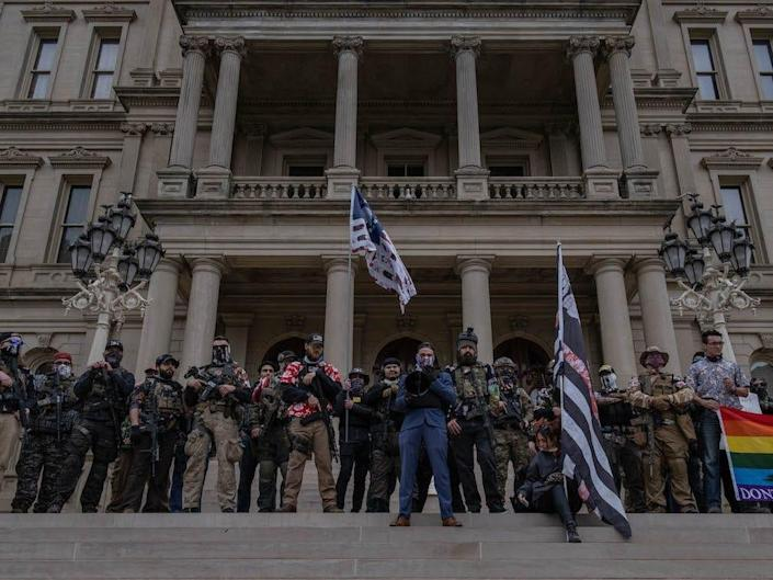 The Boogaloo Boys stand on the steps of the Capitol Building during a rally on October 17, 2020 in Lansing, Michigan.