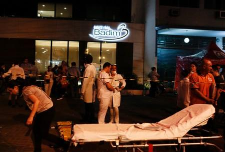 Employees are seen after a fire hit the Badim Hospital in Rio de Janeiro