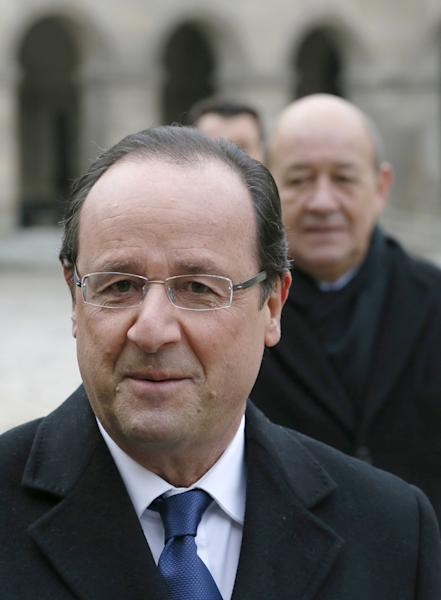 French President Francois Hollande, left, and Defense Minister Jean-Yves Le Drian reviews the troops during a military ceremony, Tuesday, Nov. 26, 2013, at the Invalides in Paris. France will send 1,000 troops to Central African Republic under an expected U.N.-backed mission to keep growing chaos at bay, the defense minister said Tuesday — boosting the French military presence in Africa for the second time this year. (AP Photo/Patrick Kovarik, Pool)