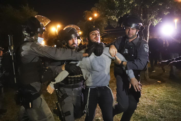 """Israeli border police detain an Israeli youth as members of """"Lahava"""", a Jewish extremist group, as they try approach to Damascus Gate to protest amid heightened tensions in the city, just outside Jerusalem's Old City, Thursday, April. 22, 2021. (AP Photo/Ariel Schalit)"""