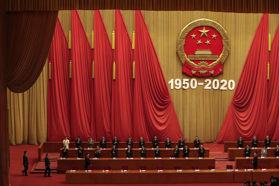Party officials applaud as Chinese President Xi Jinping, third from left in front row, followed by Premier Li Keqiang, arrives for the commemorating conference on the 70th anniversary of the Chinese army entering North Korea to resist the US army, at the Great Hall fo the People in Beijing, Friday, Oct. 23, 2020. (AP Photo/Andy Wong)