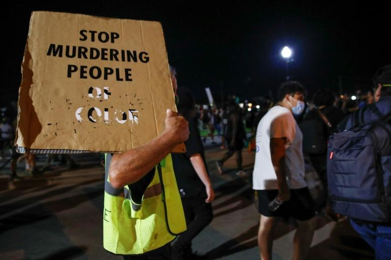 A protester holds a placard during a demonstration against the shooting of Jacob Blake in Kenosha, Wisconsin on August 26, 2020