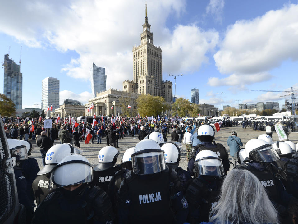 Polish police face protesters, angry over new restrictions aimed at fighting the coronavirus pandemic, in Warsaw, Poland, Saturday, Oct. 24, 2020. The protesters included entrepreneurs, far-right politicians, football fans and vaccine opponents. The clashes come amid rising social tensions and as new restrictions just short of a full lockdown took effect Saturday. (AP Photo/Czarek Sokolowski)