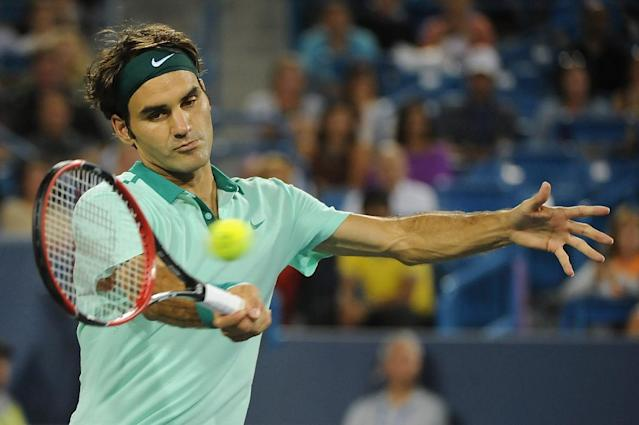 Roger Federer of Switzerland returns the ball to Milos Raonic of Canada during a match on day 8 of the Western & Southern Open at the Linder Family Tennis Center on August 16, 2014 in Cincinnati, Ohio (AFP Photo/Jonathan Moore)