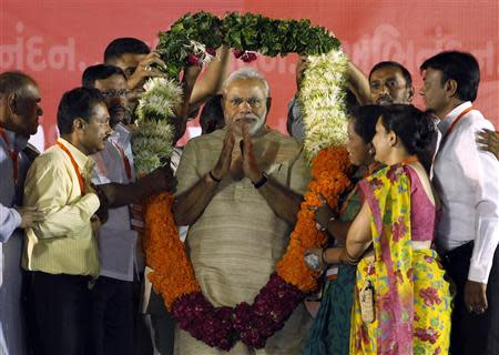 Hindu nationalist Narendra Modi, who will be the next prime minister of India, wears a garland presented to him by his supporters at a public meeting in the western Indian city of Ahmedabad May 20, 2014. REUTERS/Amit Dave