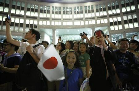 """A girl waves Japan's national flag as visitors take photos during an event titled """"Tokyo 2020 Host City Welcoming Ceremony"""", upon the delegation's return, at the Tokyo Metropolitan Government Building in Tokyo September 10, 2013."""