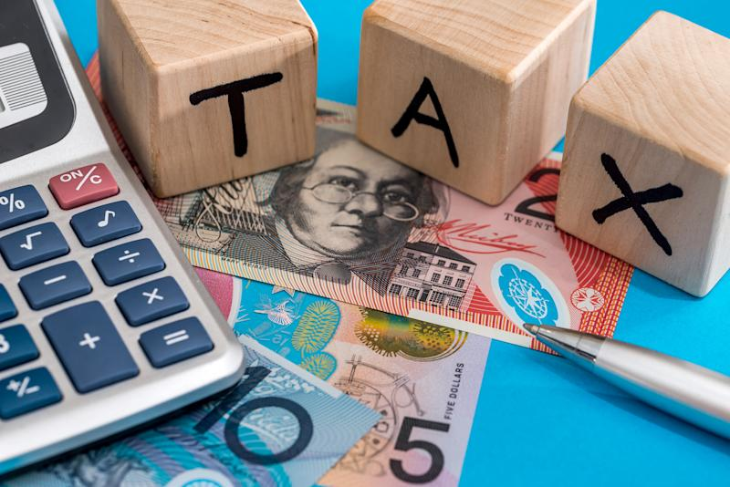 Blocks spelling out tax with Australian bank notes, pen and calculator.