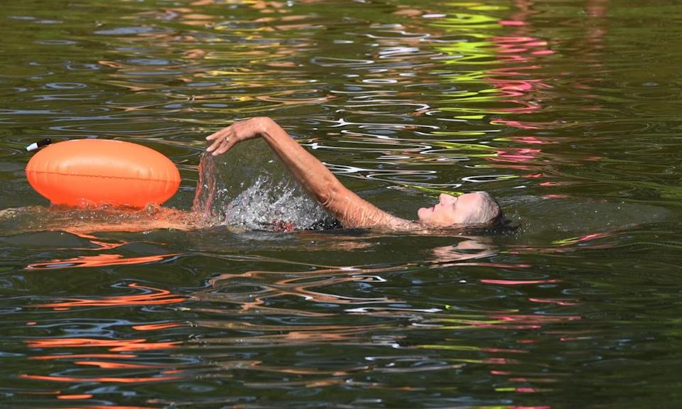 Swimmers cool down during the hot weather spell in a lake in Beckenham Place Park in south east London