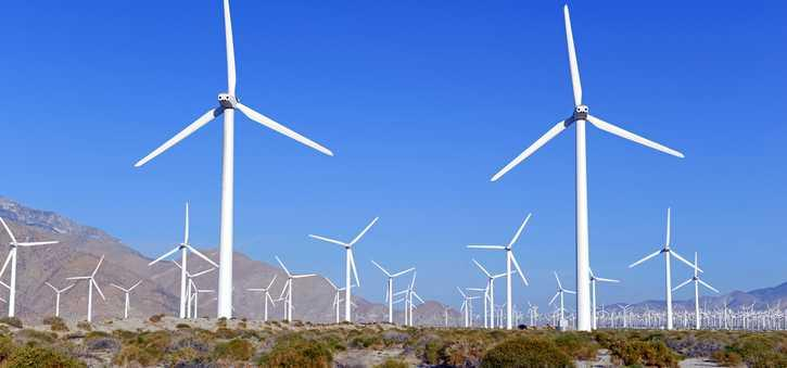 A wind farm in the desert with mountains in the background.