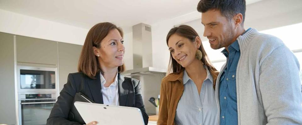 Couple with real estate agent visits house for sale