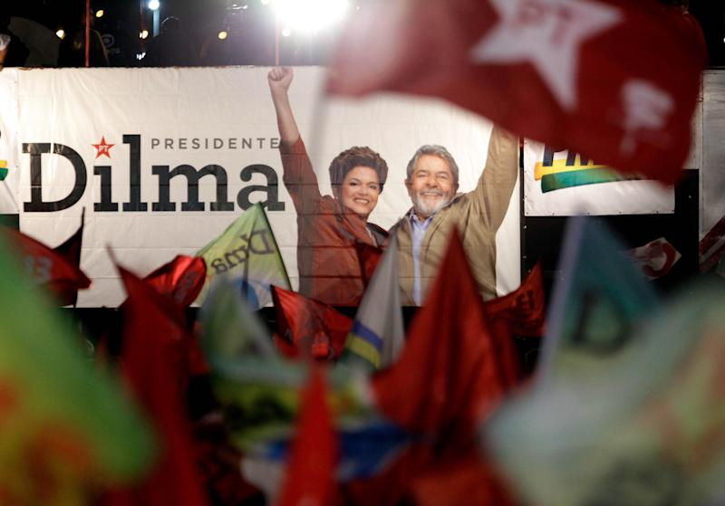 Supporters of Brazil's President-elect Dilma Rousseff wave flags of the Workers Party, in front of a campaign banner that shows her with current President Luiz Inacio Lula da Silva during the victory rally in Brasilia, Brazil, Sunday Oct. 31, 2010. Governing party candidate Dilma Rousseff was elected Brazil's president, becoming the nation's first female leader, and will take office Jan. 1. (AP Photo/Jorge Saenz)