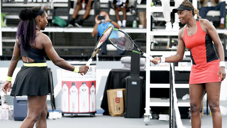 Serena Williams (L) and Venus Williams touch rackets after their tennis match.