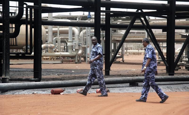 In this Tuesday, April 24, 2012 photo, Sudanese armed forces walk inside the oil production facility at the oil-rich border town of Heglig, Sudan. The African Union says Sudan must stop the aerial bombardment of South Sudan and has called on both countries to cease hostilities immediately. (AP Photo/Abd Raouf)