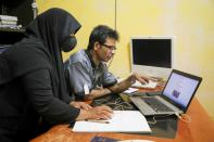 Rohingya refugee and activist Zafar Ahmad Abdul Ghani and his wife look at a computer screen displaying the threats and hate speech they received, at their home in Kuala Lumpur