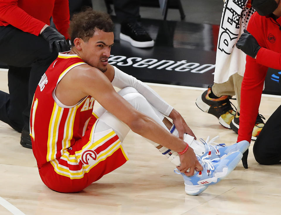 ATLANTA, GEORGIA - JUNE 27: Trae Young #11 of the Atlanta Hawks holds his ankle after an injury during the second half in game three of the Eastern Conference Finals against the Milwaukee Bucks at State Farm Arena on June 27, 2021 in Atlanta, Georgia. NOTE TO USER: User expressly acknowledges and agrees that, by downloading and or using this photograph, User is consenting to the terms and conditions of the Getty Images License Agreement. (Photo by Todd Kirkland/Getty Images)