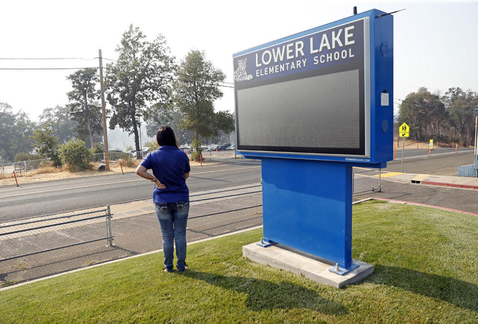 LOWER LAKE – AUGUST 18: Lower Lake Elementary School Director of Maintenance Operations' Stephanie Hunt watches as the Cache Fire is contained across Lake Street from the school in Lower Lake, Calif., on Wednesday, August 18, 2021. (Scott Strazzante/San Francisco Chronicle via Getty Images)