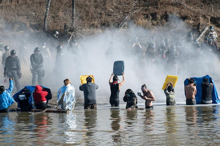 <p>Police use pepper spray against people standing in the water of a river during a protest against the building of a pipeline on the Standing Rock Indian Reservation near Cannonball, N.D., on Nov. 2, 2016. (Photo: Stephanie Keith/Reuters) </p>